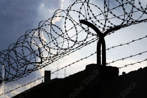 Dramatic clouds behind barbed wire fence on a prison wall Poster