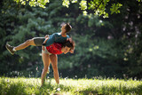 Young couple stretching and relaxing after jogging outdoor.Green environment.