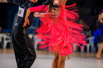 athletes couple of dancers on ballroom dance contest. bright red dress girl
