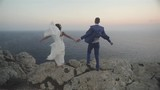 Wedding Couple Stands On A Cliff Above A Sea