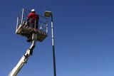 Operaio su cestello elevatore con lampione led a risparmio energetico - 108134556