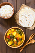 Постер, плакат: Pumpkin mangold potato and tomato curry dish in wooden bowl with homemade chapati flatbread and rice photographed with natural light