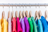 Fototapety Fashion clothes on clothing rack - bright colorful closet. Closeup of rainbow color choice of trendy female wear on hangers in store closet or spring cleaning concept. Summer home wardrobe.