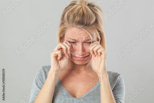 drama concept - sad young blond woman crying with big tears comforting her break down and sorrow, grey background studio.