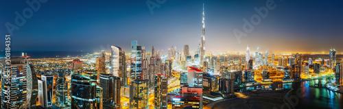 Staande foto Dubai Aerial panoramic view of a big futuristic city by night. Business bay, Dubai, United Arab Emirates. Nighttime skyline.
