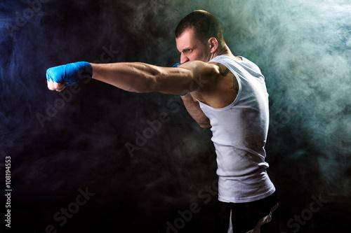 Staande foto Muscular kickbox or muay thai fighter punching in smoke