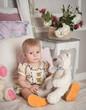 Obrazy na płótnie, fototapety, zdjęcia, fotoobrazy drukowane : Маленькая девочка сидит на кровати с плюшевым белым мишкой