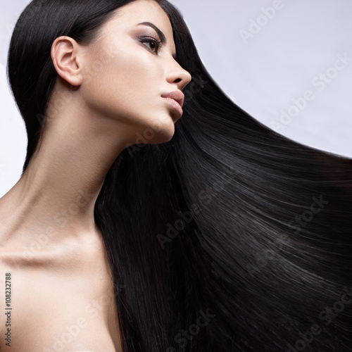 Fototapeta Beautiful brunette girl in move with a perfectly smooth hair, and classic make-up. Beauty face.