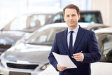 Fototapety Smiling salesman reading a document at new car showroom