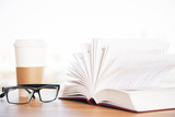 Open book, glasses and coffee