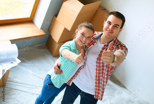 Young couple happy in their new modern design house showing thumbs up stock photo and royalty - Young couple modern homes ...