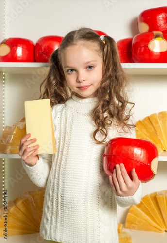 Beautiful little girl with cheese in the hands front of shelves   Poster