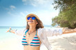 Happy beautiful young woman in a hat and sunglasses on the shore