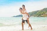 Fototapety beautiful young couple walking along the shore of a tropical sea