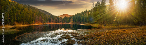 panorama of crystal clear lake near the pine forest in  mountains at sunset - 108294378