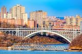 Henry Hudson Bridge spans Spuyten Duyvel Creek, in New York City. Harlem apartment buildings shine under the late afternoon light. - 108315996