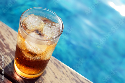Poster A glass of ice cola at pool with vintage filter background