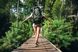 Fototapety Young woman with backpack traveling across hanging bridge in tropical forest