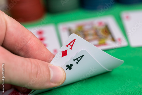 poker player holding playing cards with chips and money плакат