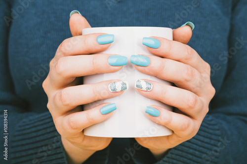 Manicure - Beauty treatment photo of nice manicured woman fingernails holding a cup. Nice blue polish and flower design on accent nail. © tamara83
