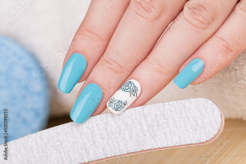 Manicure - Beauty treatment photo of nice manicured woman fingernails with blue polish and flower design on accent nail. © tamara83