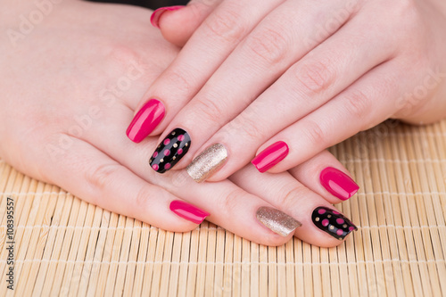 Manicure - Beauty treatment photo of nice manicured woman fingernails. Very nice feminine nail art with nice pink, gold and black nail polish. © tamara83