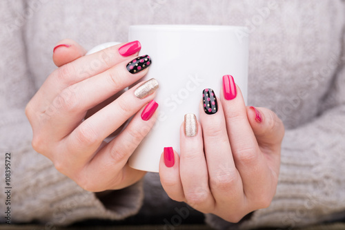 Manicure - Beauty treatment photo of nice manicured woman fingernails holding a cup. Very nice feminine nail art with nice pink, gold and black nail polish. © tamara83