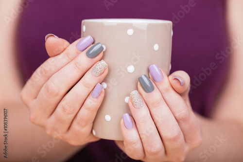 Manicure - Beauty photo of nice manicured woman fingernails holding a cup. Very nice feminine nail art with nice purple,silver and grayish nail polish. © tamara83