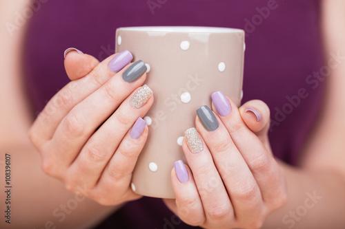 Manicure - Beauty photo of nice manicured woman fingernails holding a cup. Very nice feminine nail art with nice purple,silver and grayish nail polish. © tamara83