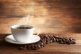 Fototapety Cup of coffee with grains on wooden background