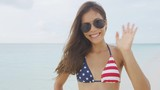 American Asian woman waving hello with hand at camera wearing USA flag bikini and sunglasses happy on summer beach vacation. United States of America 4th of july patriotic celebration concept.