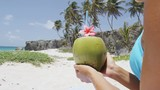Fresh coconut water with straw on Caribbean beach in Barbados vacation. Unrecognizable woman in Barbados holding young green tropical fruit for healthy snack during summer holidays.