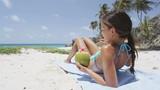 Luxury beach vacation tropical destination woman sun tanning drinking coconut water. Sunbathing bikini woman relaxing lying down in Barbados, Caribbean travel holiday.