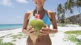 Happy suntan bikini girl drinking healthy coconut water for weight loss on tropical beach vacation. Cute woman sipping from a straw in a fresh green fruit on Caribbean destination.