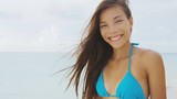 Beach summer vacation bikini woman smiling on tropical background. Close up portrait of beautiful young Asian multiracial woman with hair in the wind on tropical beach slow motion.
