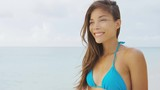 Summer holiday. Attractive Asian chinese bikini model enjoying tropical beach vacation with wind in the hair living a healthy lifestyle. Gorgeous model relaxing in the wind slow motion.