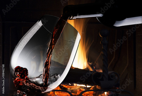 glass with red wine near the fireplace Poster