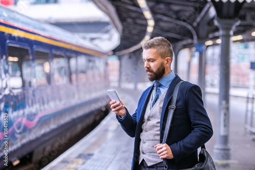 Hipster businessman with smartphone, waiting at the train platfo Poster