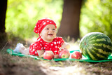 Little girl in red dress sitting near the watermelon and apples