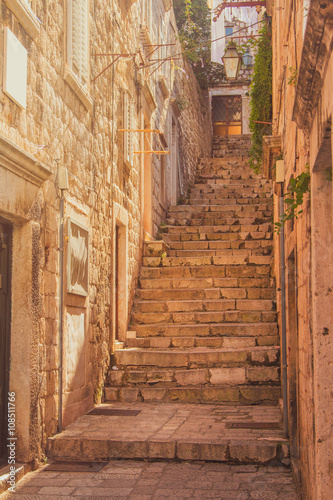 Fototapeta Narrow street and stairs in the Old Town in Dubrovnik, Croatia, Mediterranean ambient, warm filter, lens flare