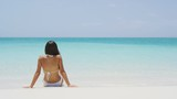 Beach vacation people - woman relaxing looking at perfect paradise with turquoise ocean water. Girl in bikini sunbathing on travel holidays on luxury island. SLOW MOTION shot on RED EPIC.