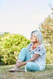 Alte Frau sitzt im Park und hat Schmerzen
