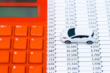 Image of auto related expense, with calculator, spreadsheet, and toy car