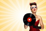 Retro play / Vintage photo of glamorous pinup girl wearing long gloves and dressed in a red sexy corset, holding LP vinyl record on colorful abstract cartoon style background.