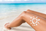 Sunscreen sun drawing lotion on suntan legs relaxing tanning on tropical beach holiday. Women lower body lying with sunblock cream in shape for skin cancer sunburn care concept.