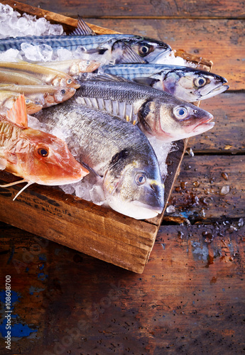Fresh raw fish on cutting board over old table
