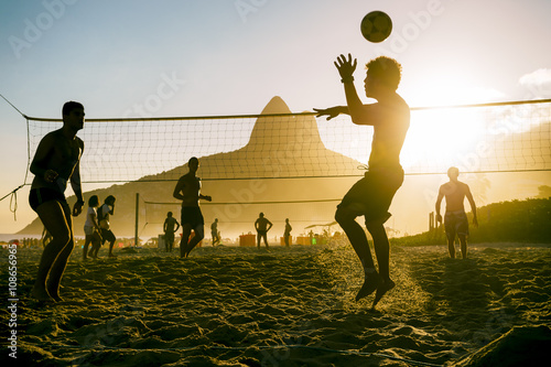 Silhouettes of Brazilians playing beach futevolei (footvolley), a sport combinin