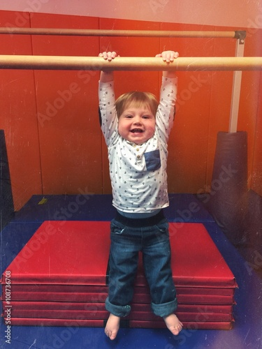 Baby In Gym On Gymnastic Bar Trying To Do Pullup And Is Hanging