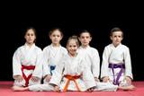 Fototapety Children in kimono sitting on tatami on martial arts seminar. Selective focus