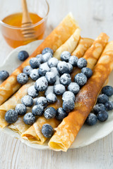 pancakes with blueberries on wooden surface